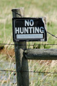 Ein Stacheldrahtzaun an dem ein Schild hängt auf dem NO HUNTING steht