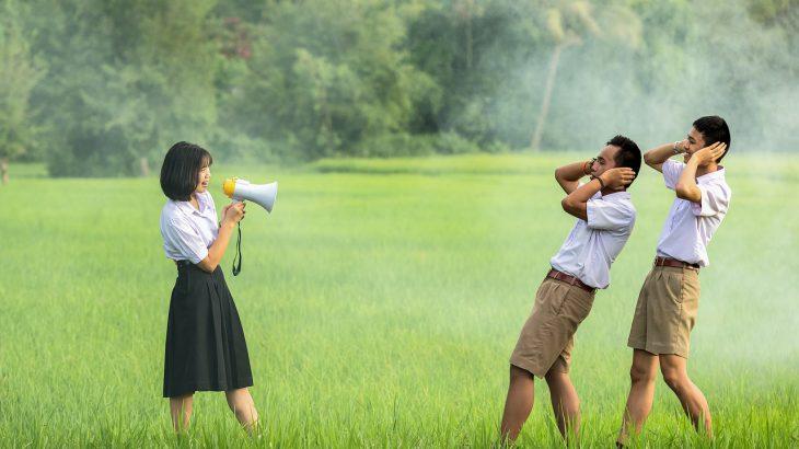 Eine Frau die mit einem Megaphone zwei Männer beschallt, die sich die Ohren zuhalten.