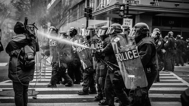 Pfeffersprayende Polizisten auf einer Demonstration