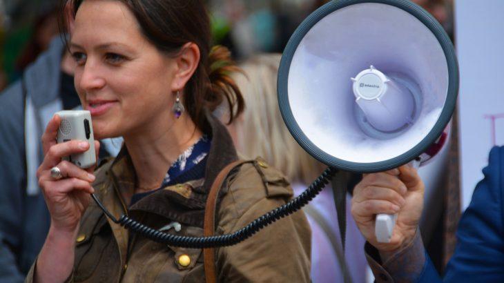 Eine Frau mit einem Megaphone in der Hand