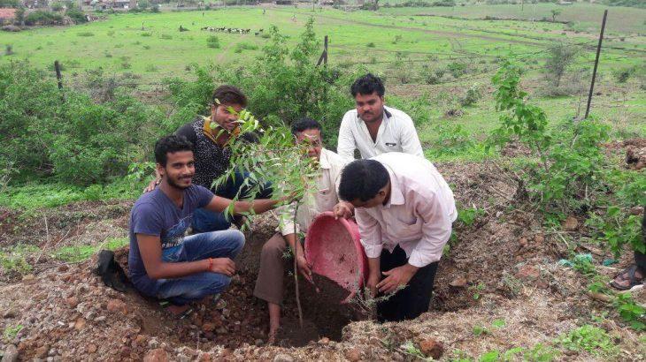 Fünf Inder, die einen Baum pflanzen.