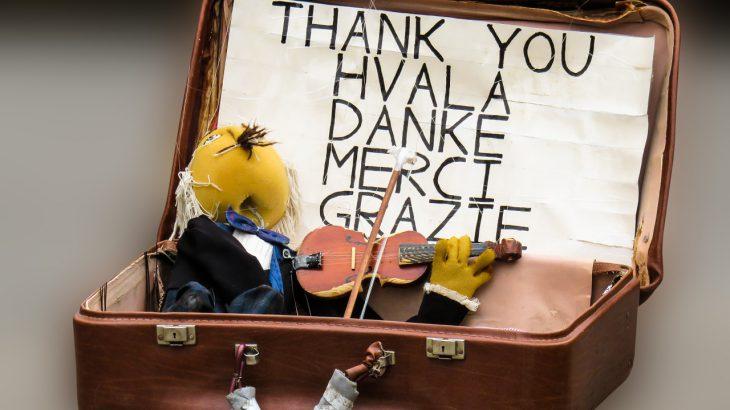 Ein Koffer in dem in vielen Sprachen Danke steht. Darin sitzt eine Geige spielende Puppe.