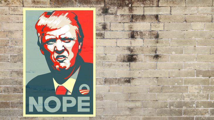 """Ein Plakat von Donald Trump an einer Hauswand auf der """"NOPE"""" steht"""
