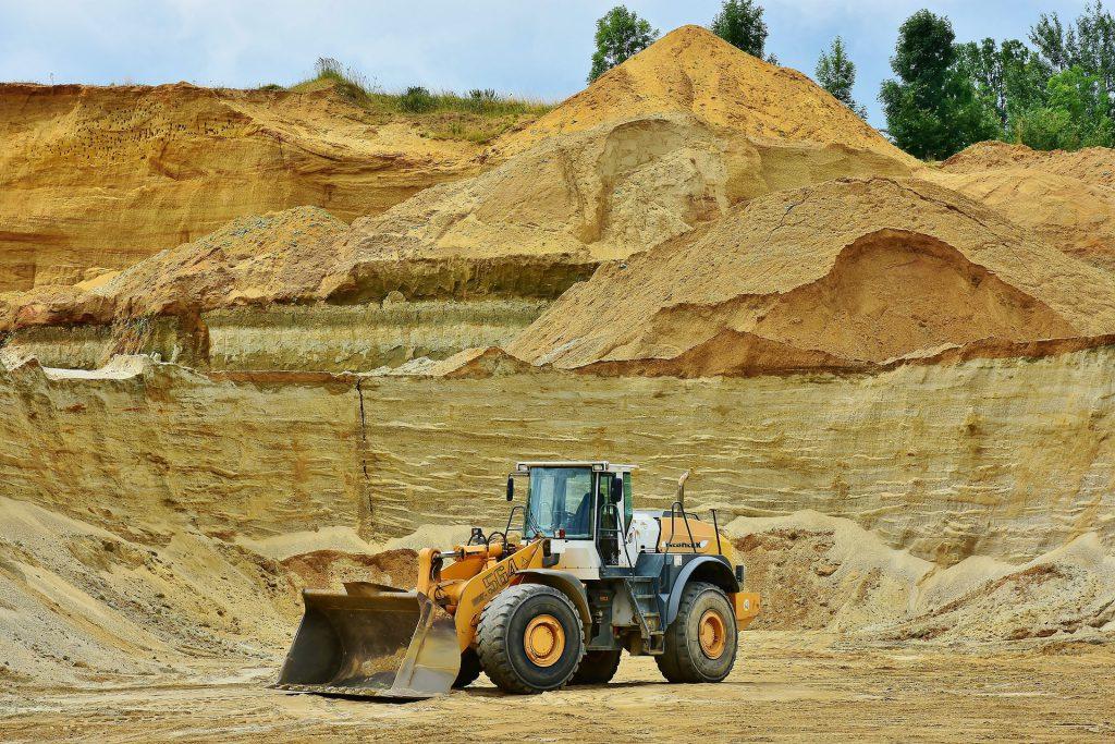 Ein Schaufelbagger vor einem großen Haufen Sand