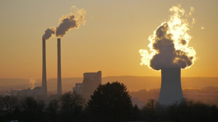Ein Kohlekraftwerk in der Abenddämmerung mit rauchendem Schlot