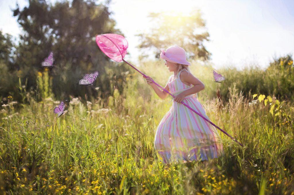 Ein Mädchen, das fröhlich auf einer Wiese Schmetterlinge mit einem Käscher fängt