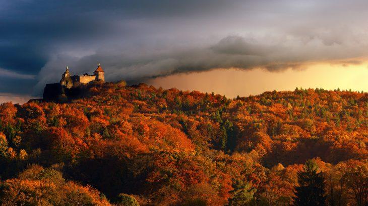 Ein schönes Bergpanorma das Laubbäume und eine Burg zeigt