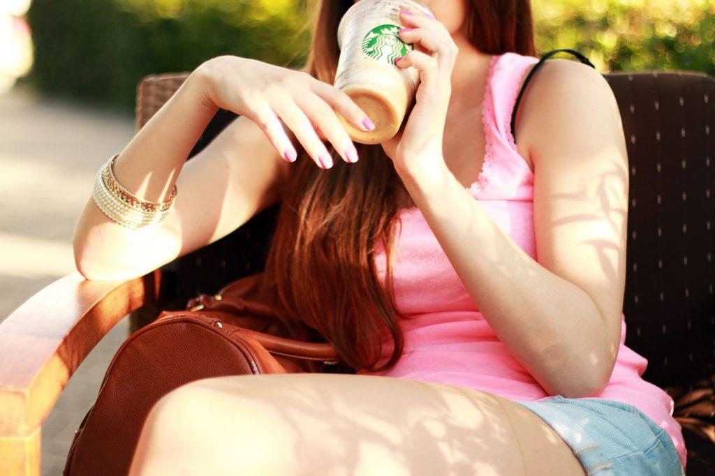Eine Frau, die einen Starbucks-Shake aus einem Einwegbecher trinkt