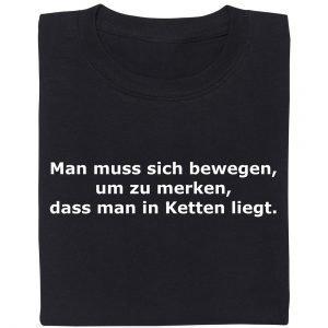 """Ein T-Shirt mit der Aufschrift """"Man muss sich bewegen, um zu merken, dass man in Ketten liegt"""""""