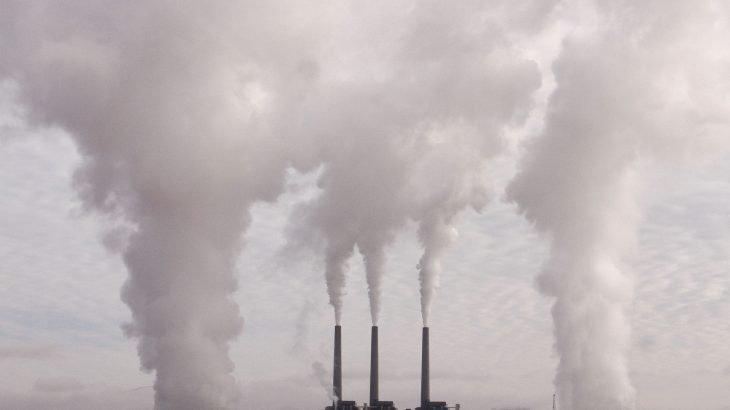 Eine Fabrik aus deren Schornsteinen enorm Viel Rauch entweicht