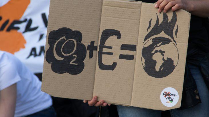 """Ein Protestschild auf dem Steht """"CO2 + € = Brennende Erde"""""""