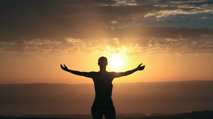 Ein Mensch der mit gestreckten Armen vor einem Sonnenaufgang steht.