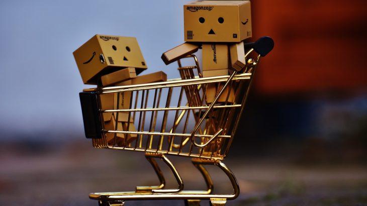 Zwei Amazon Paketmännchen sitzen in einem Einkaufskorb
