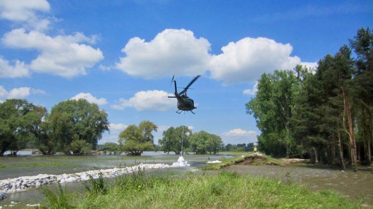 Helikopter lässt Sandsäcke in Hochwasser ab